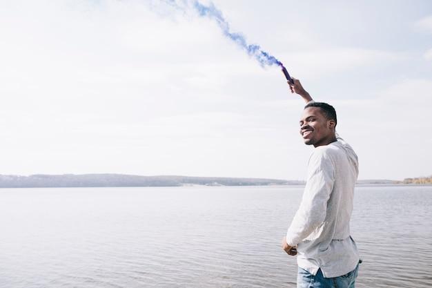 Uomo con la torcia di fumo sulla riva