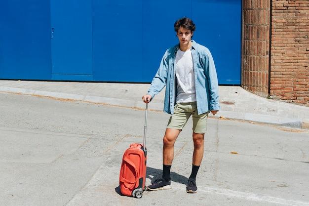 Uomo con la valigia di viaggio in posa sulla strada