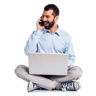 Uomo con laptop che parla al cellulare
