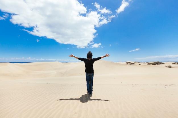 Uomo con le braccia spalancate su un paesaggio di dune del deserto. concetto di viaggi e vacanze.