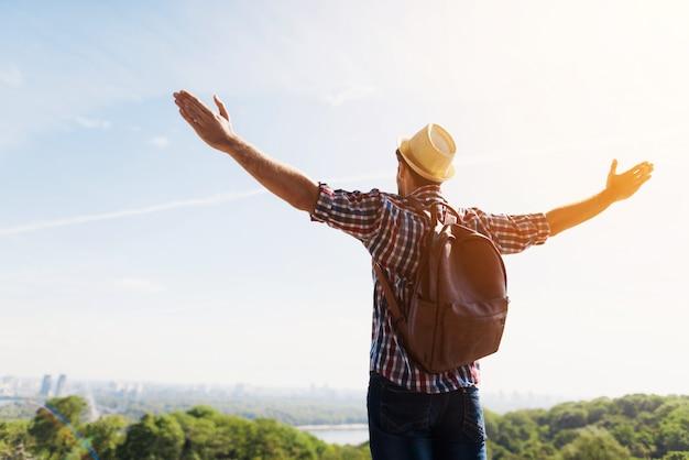 Uomo con le braccia tese contro il bellissimo paesaggio verde