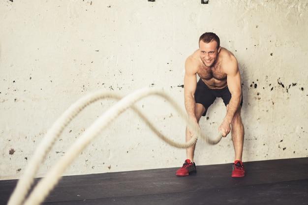 Uomo con le corde di battaglia che si esercitano nella palestra di forma fisica