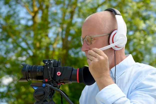 Uomo con le cuffie, usando una fotocamera dslr