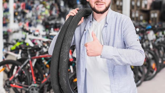 Uomo con le gomme della bicicletta che gesturing pollice in su