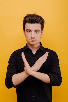 Uomo con le mani incrociate su sfondo giallo
