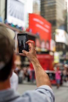 Uomo con lo smartphone che prende selfie