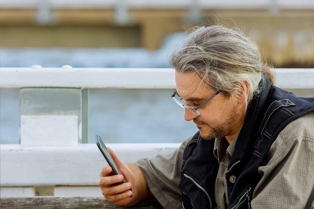 Uomo con lo smartphone sulla strada della città