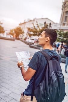 Uomo con lo zaino che cammina sulla strada con la mappa