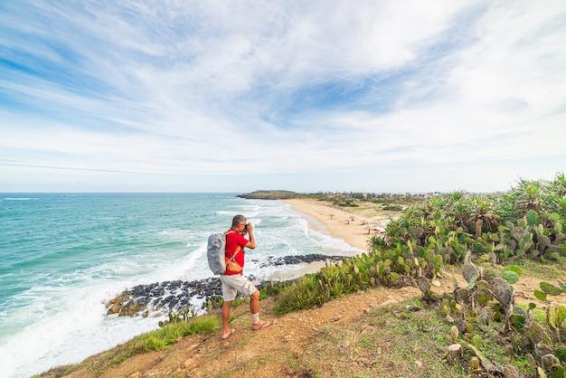Uomo con lo zaino che esamina costa tropicale dalla scogliera qui sopra. destinazione di viaggio in vietnam, provincia di phu yen tra da nang e nha trang. bai xep splendida spiaggia di sabbia