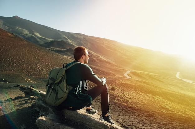 Uomo con lo zaino che si siede sulla roccia al tramonto sulla montagna dell'etna del vulcano in sicilia