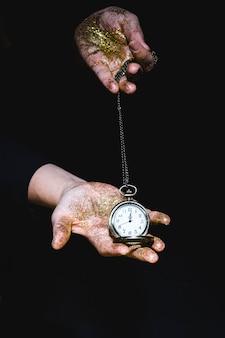 Uomo con luccichii che mostra l'orologio da tasca