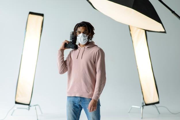 Uomo con maschera e macchina fotografica