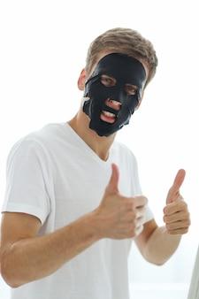 Uomo con maschera facciale nera, carbone purificante per la pelle. concetto di bellezza