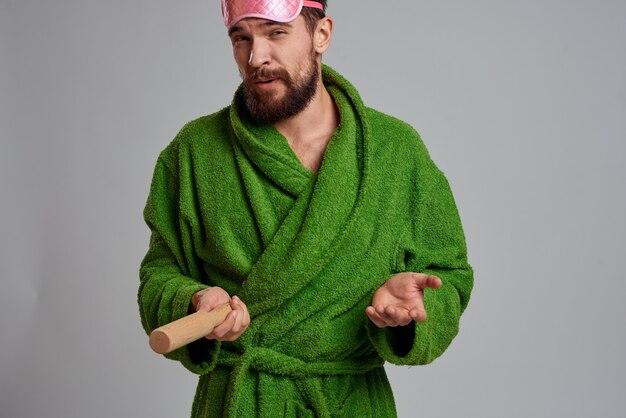Uomo con mattarello indossando accappatoio verde