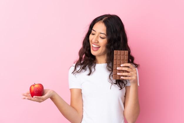 Uomo con mela in una mano e cioccolato nell'altra