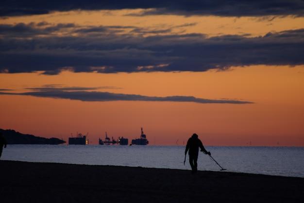Uomo con metal detector al mattino, sulla spiaggia