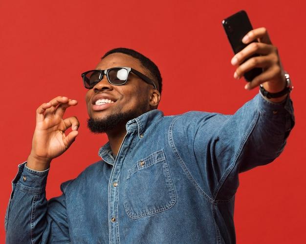 Uomo con occhiali da sole prendendo selfie