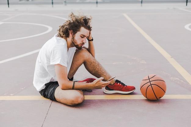 Uomo con pallacanestro che si siede in tribunale per mezzo del cellulare