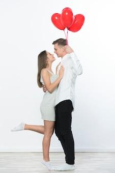 Uomo con palloncini cuore abbracciando la donna