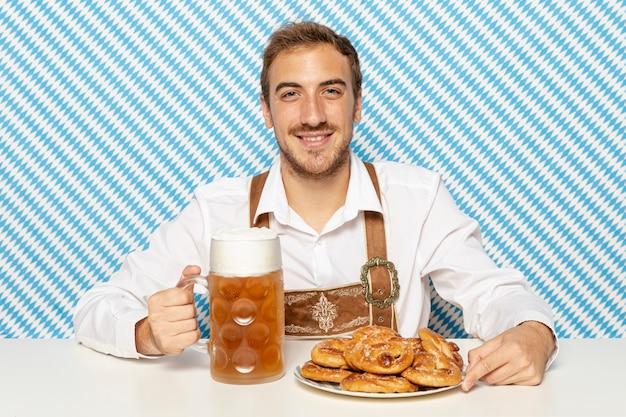 Uomo con piatto di salatini e birra
