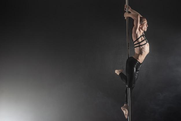 Uomo con pilone. ballerino maschio del palo che balla su un fondo nero