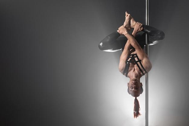 Uomo con pilone. ballerino maschio pole dancing