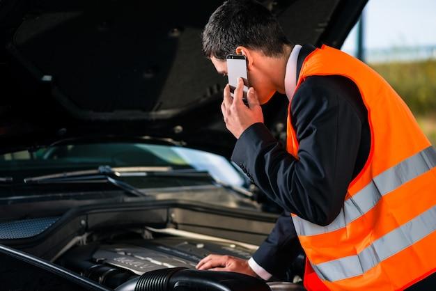Uomo con problemi con il motore dell'auto che chiama il servizio di riparazione