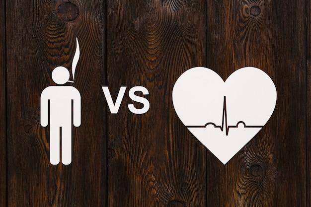 Uomo con sigaretta e cuore con ecocardiogramma.