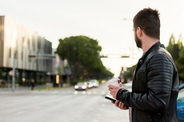 Uomo con smartphone e caffè attraversando la strada