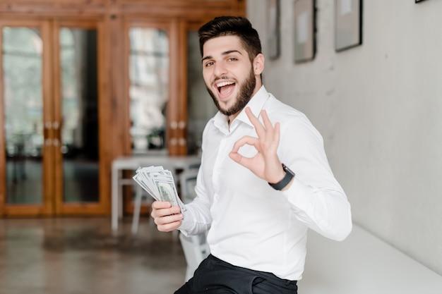 Uomo con soldi che mostrano gesto giusto