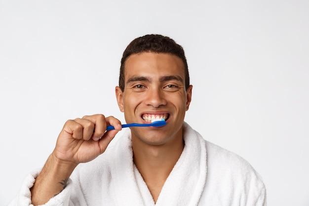 Uomo con spazzolino da denti. uomo africano che tiene uno spazzolino da denti con lo spazzolino da denti e che sorride mentre stando