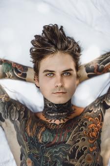 Uomo con tatuaggi colorati in posa su un foglio bianco