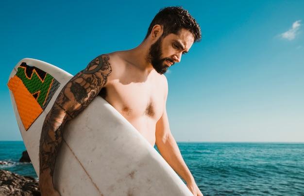 Uomo con tavola da surf a piedi vicino al mare
