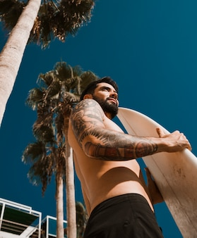 Uomo con tavola da surf sul resort