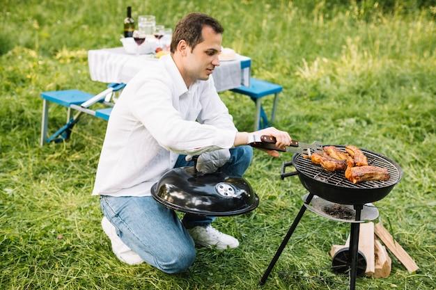 Uomo con un barbecue in natura
