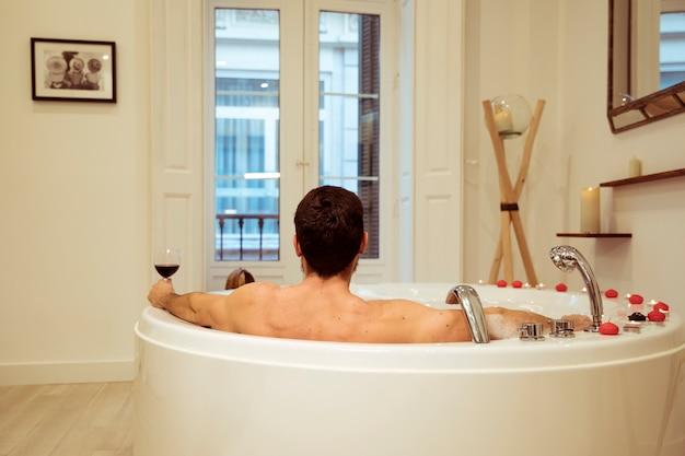 Uomo con un bicchiere di bevanda nella vasca idromassaggio con candele accese