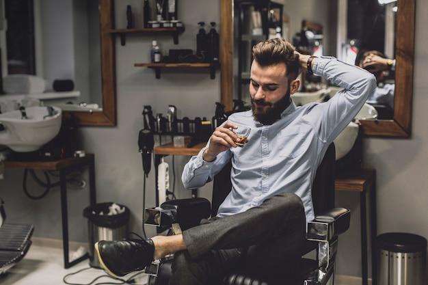 Uomo con un bicchiere di liquore nel negozio di barbiere