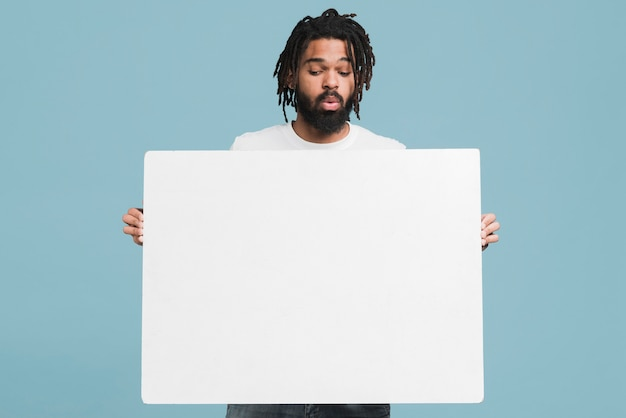 Uomo con un cartello bianco