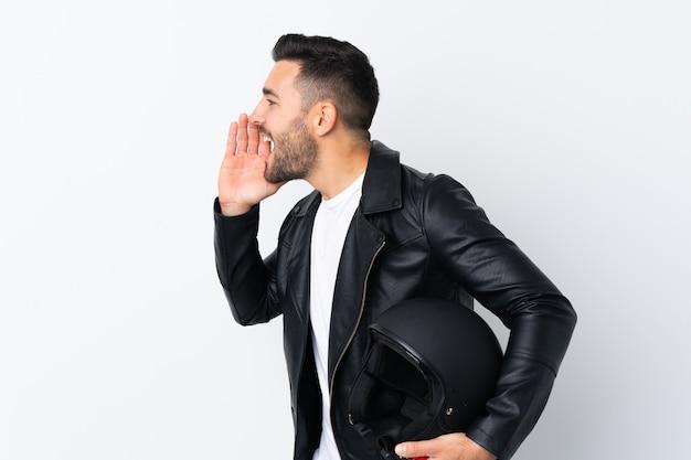 Uomo con un casco da motociclista che grida con la bocca spalancata
