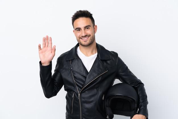 Uomo con un casco da motociclista che saluta con la mano con l'espressione felice