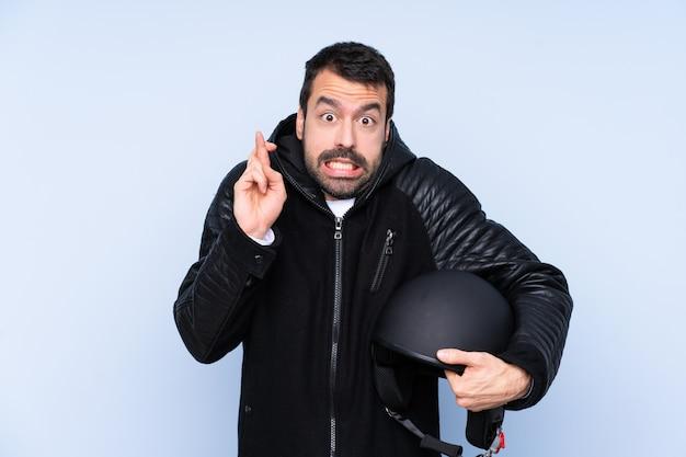 Uomo con un casco da motociclista con le dita incrociate e che desiderano il meglio