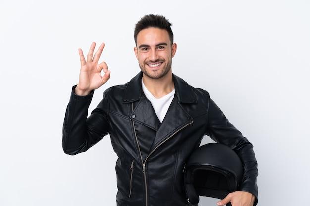 Uomo con un casco del motociclo che mostra segno giusto con le dita