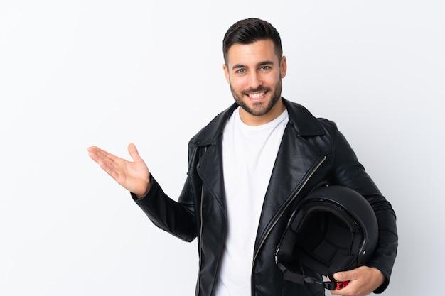 Uomo con un casco del motociclo che tiene copyspace immaginario sulla palma