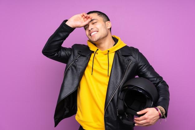 Uomo con un casco del motociclo isolato sulla risata viola della parete