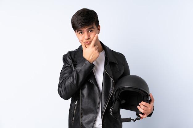 Uomo con un casco del motociclo sopra il blu isolato che pensa un'idea