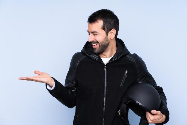 Uomo con un casco del motociclo sopra il copyspace isolato della tenuta della parete con due mani