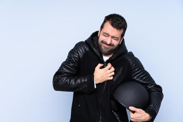 Uomo con un casco del motociclo sopra la parete isolata che ha un dolore nel cuore