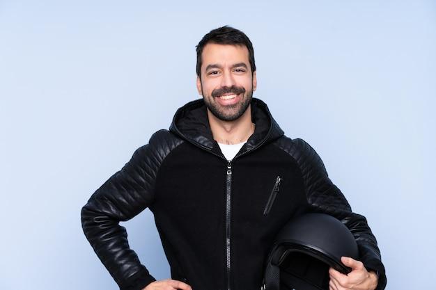 Uomo con un casco del motociclo sopra la parete isolata