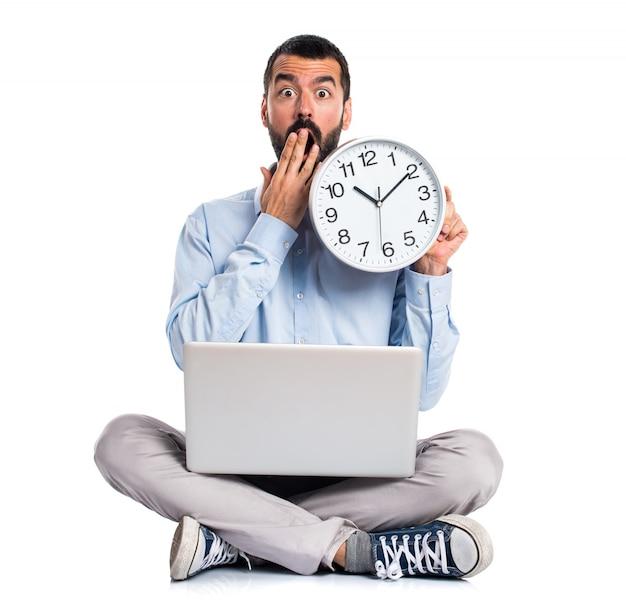 Uomo con un computer portatile in possesso di un orologio