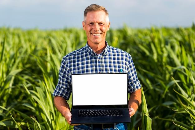 Uomo con un computer portatile in un modello del campo di mais